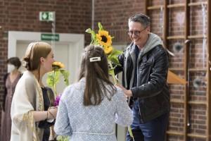 Schulleiter Alexander Delport übergibt Schülerinnen der Abschlussklasse Sonnenblumen